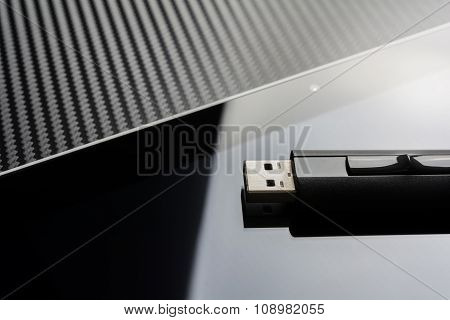 Usb Storage Flash Drive Lying On Blank Business Tablet Screen With Reflection In Front Of Carbon