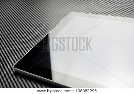 Blank Business Tablet With Reflection Lying On Carbon Layer
