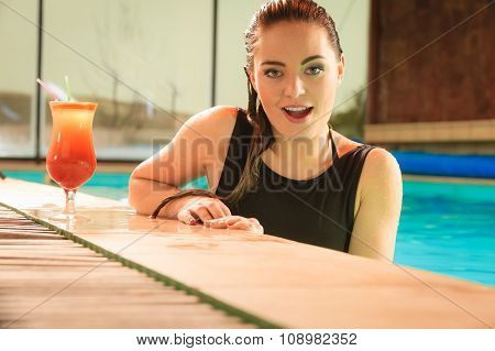 Woman With Cocktail Drink At Swimming Pool Edge.