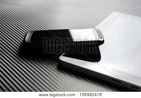 Business Smartpone With Reflection Leaning On Tablet With Blank Screen Above A Carbon Layer