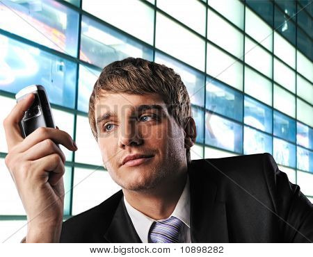 Young businessman with mobile phone over abstract background
