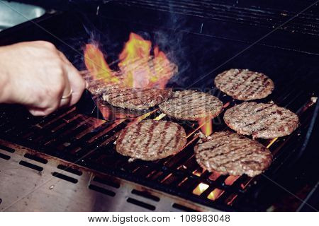Chef is cooking burgers on a gas grill