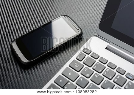 Black Smartphone With Reflection Lying Left To Business Notebook Keyboard, All Above A Carbon Layer