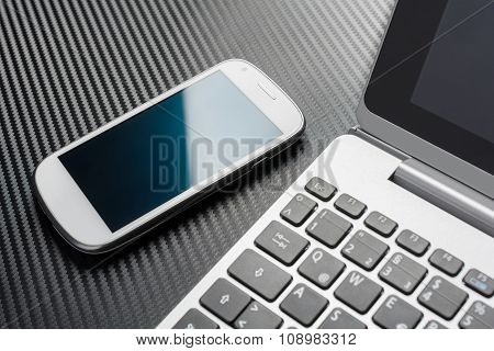 White Business Mobile With Reflection Lying Left To A Notebook Keyboard, All On A Carbon Layer