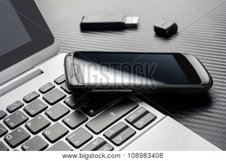 Blank Black Smartphone With Reflection Leaning On A Business Notebook Keyboard Near An USB Device