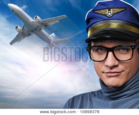 Handsome young pilot against flying plane