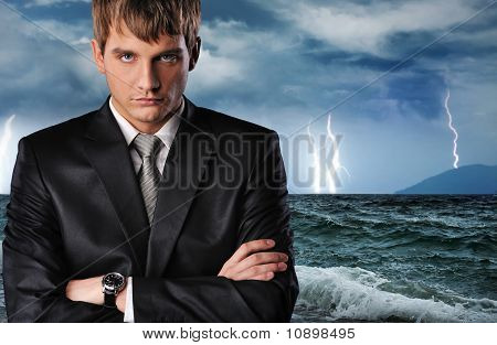 Businessman over dark stormy sky