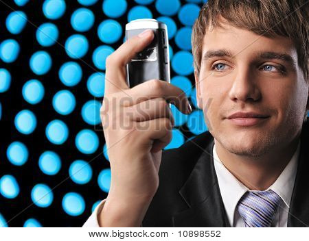 Young businessman holding mobile phone over abstract background