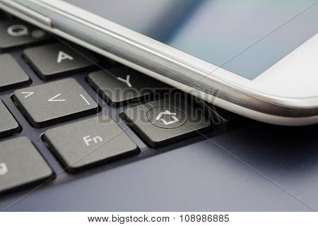 A White Mobile With Reflection On A Keyboard With Home Button