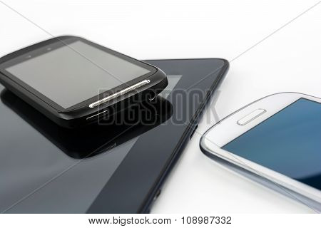Black Smartphone On Black Tablet With White Mobile Besides