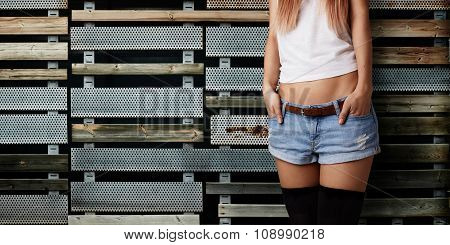 Half Body Shot Of A Cheerful Stylish Woman In Denim Shorts And White T-shirt, Against Texture Wall B