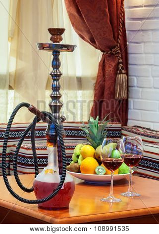 Hookah, glasses of wine and fruits