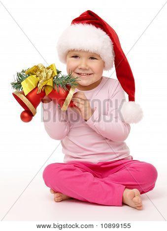 Little Girl Holds Red Christmas Bells