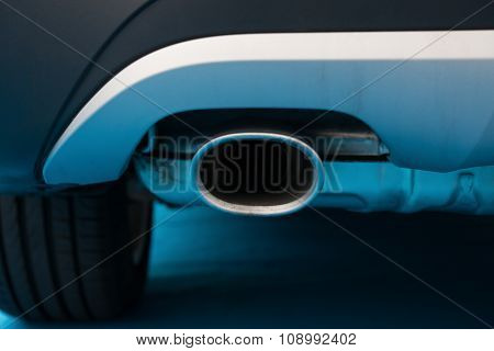Exhaust Pipe Of A Black Car On Blue Carpet
