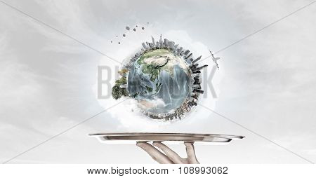 Hand of waiter holding tray with Earth planet. Elements of this image are furnished by NASA