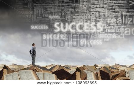 Young confident businessman with arms on waist standing on pile of old books