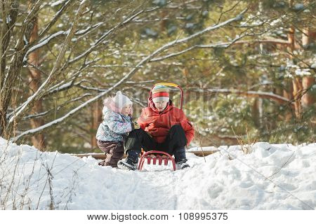Sibling children getting ready for sliding down snowy hill on wooden sled with metal runners