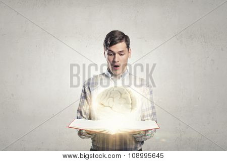 Shocked man holding opened book with brain picture