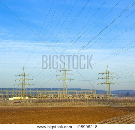 Electrical Tower In Rural Landscape With Bale Of Straw
