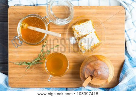 Honey in glass jar,  honeycombs wax and cup of tea