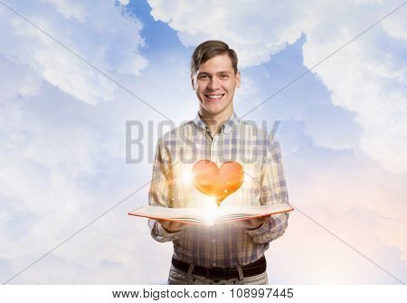 Young man with opened book and red heart on pages