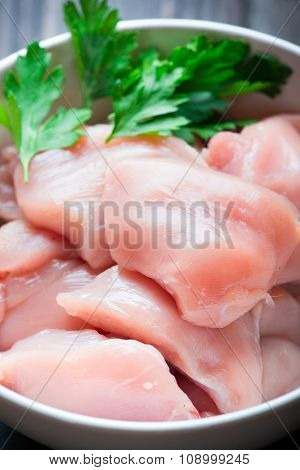 Raw cut chicken fillet with spices and herbs. Small pieces of meat