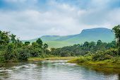 Постер, плакат: River In The Jungle Small River In Jungle Under The Cloudy Sky Through Hills And Mountains The Sma
