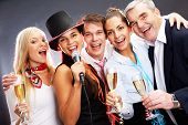 stock photo of christmas party  - Photo of businesspeople with flutes of champagne singing at Christmas party - JPG