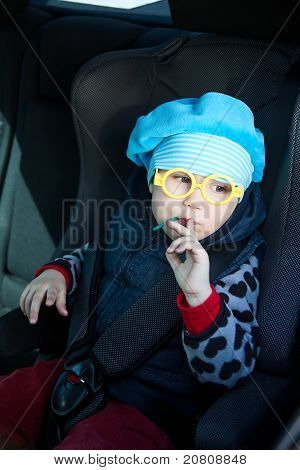 Little Child Sitting In Carseat In Vehicle With Lollipop. Funny Glasses
