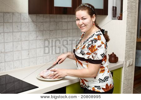 Beautiful Happy Smiling Woman In Kitchen Interior With Chicken