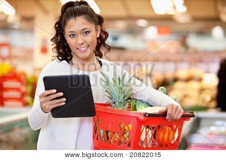 Woman with digital tablet holding fruit basket in shopping centre and looking at camera