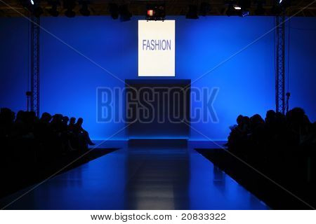 podium before showing new collection of clothing, dark silhouettes of audience