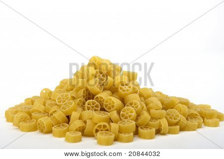 Raw wagon wheel pasta noodles in a pile
