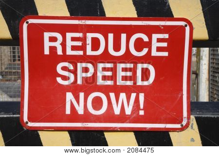 Old British Reduce Speed Now Sign On A Barrier.