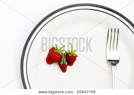 Strawberries and fork on a plate