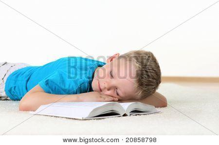 kleiner Junge im blauen T-shirt mit einem Buch im studio