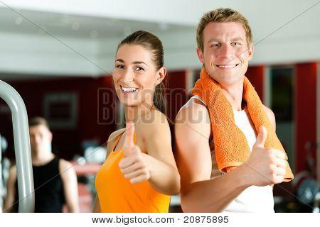 Pareja deportiva en gimnasio y fitness club mirando al espectador