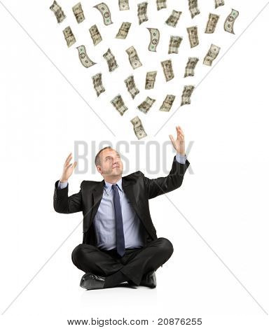 Money falling from the air into the hands of a young smiling businessman isolated on white background