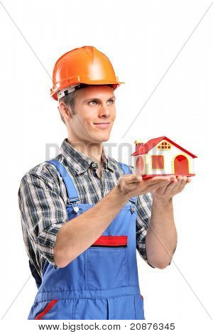 A male construction worker wearing helmet and holding a model house isolated on white background