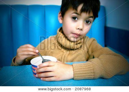Young Boy Enjoying Tub Of Icecream