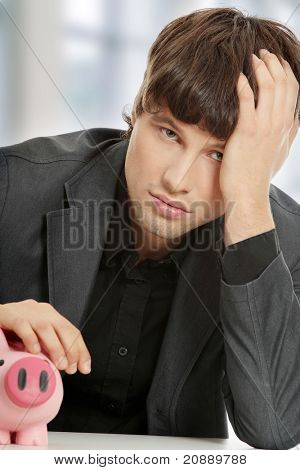Young depressed businessman holding piggy bank. Economy crisis concept