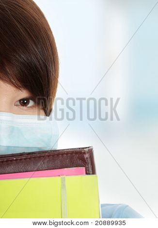 Close up portrait of young  student woman with mask on her face. She is defending her self from viruses.