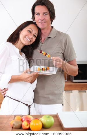 A couple eating fruit skewers