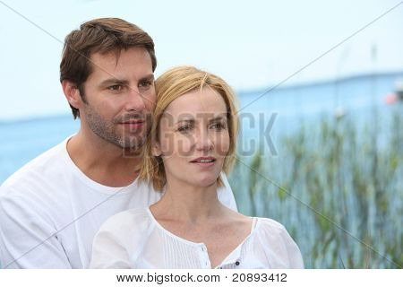 couple posing in front of reeds and the blue ocean