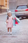 Girl Goes Shopping With Branded Packages Or Shopping Bags In City. Shopping With Child While Walking poster