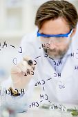 Confident middle-aged scientist writing structural chemical formula on a glass board while working a poster