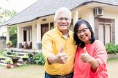 Happy elderly couple showing thumbs up in front of their new residential property poster