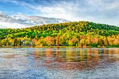 Chicoutimi River In Saguenay, Quebec, Canada With Riverfront Houses And Forest During Sunset With Co poster