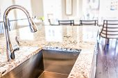 New Modern Faucet And Kitchen Room Sink Closeup With Island And Granite Countertops In Model House, poster