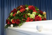 stock photo of coffin  - A white coffin with a flower arrangement in a mortuary - JPG